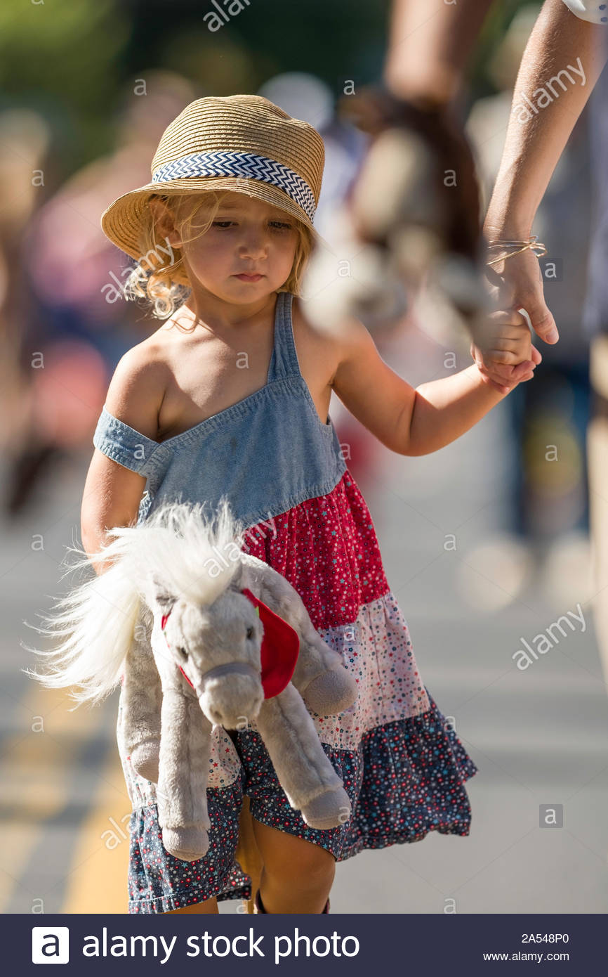 Woman holding the hand of a young girl walking down Baldwin Avenue during the second leg of the stick horse race Stock Photo
