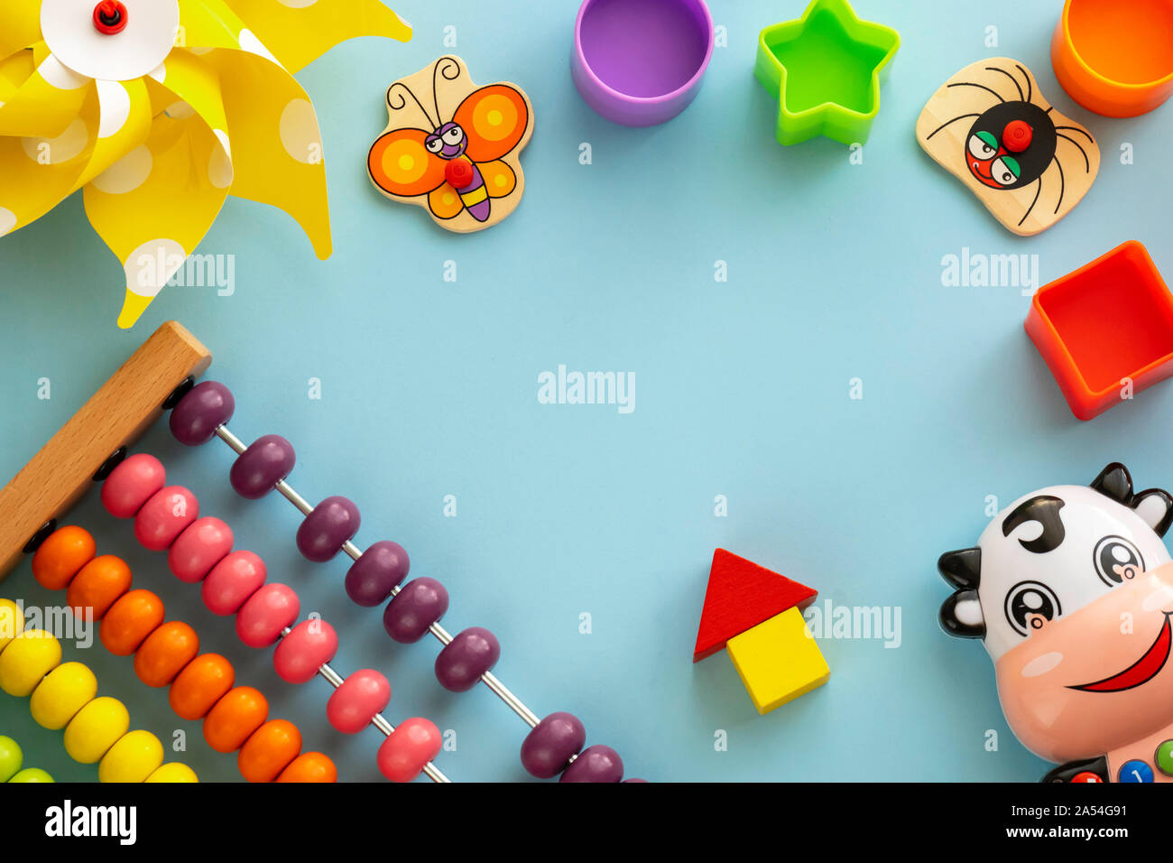 Top view on children's educational games, frame from kids toys on blue paper background. Сubes, stars, circles, cow, pinwheel, abacus, cute butterfly, spider. Flat lay, copy space.  Stock Photo