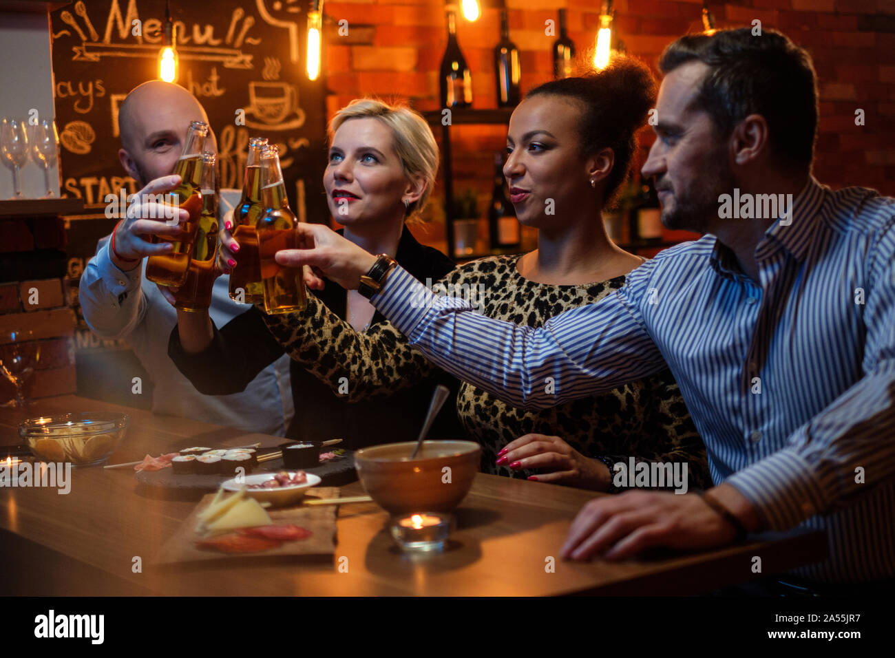 Group Of Friends Watching Tv In A Cafe Behind Bar Counter Stock Photo Alamy