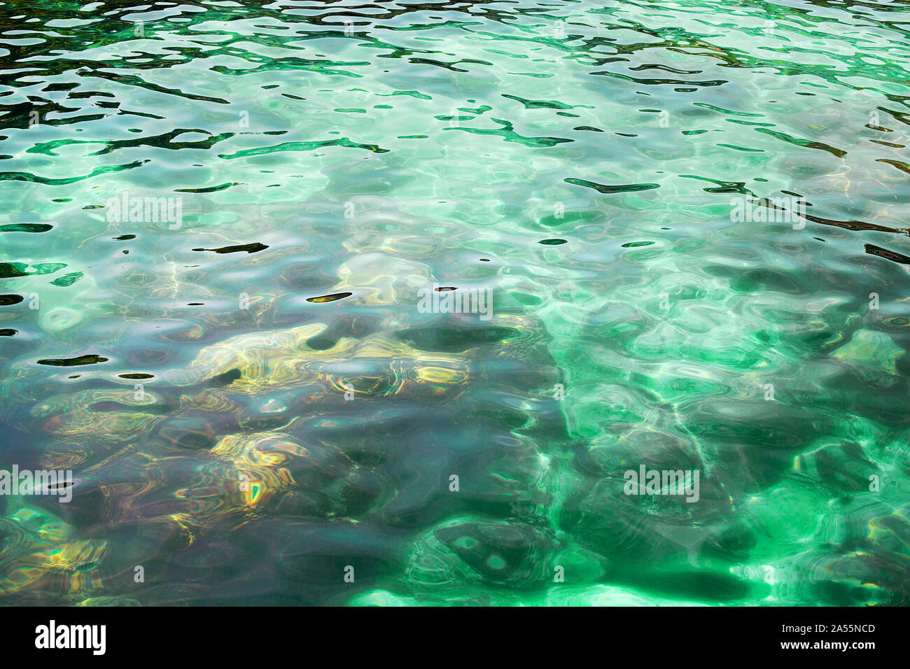Blue crystal clear sea water, stones texture background, turquoise transparent ocean, underwater coral reef surface close up sun light rays reflection Stock Photo