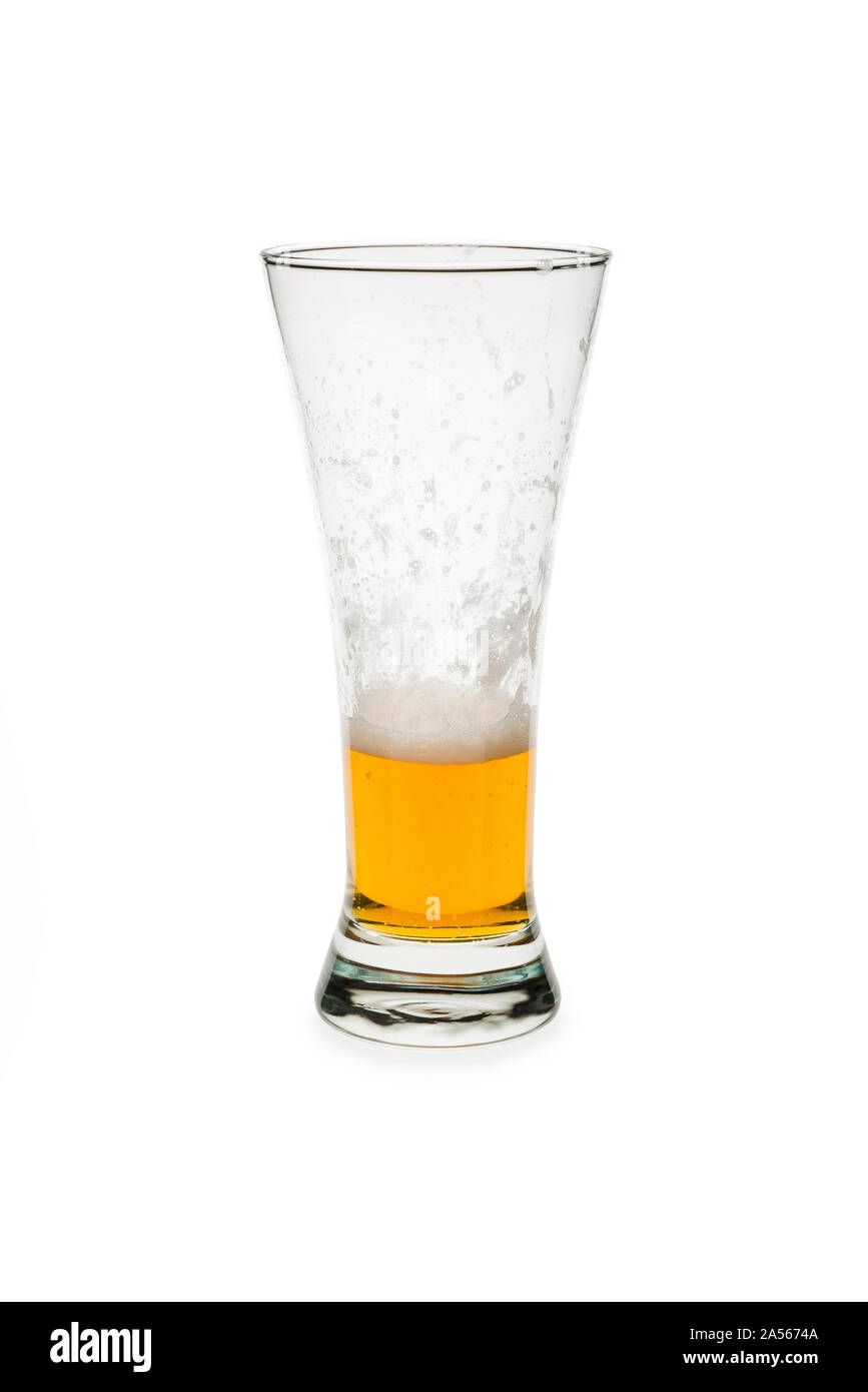 Partly consumed beer in a pilsner glass isolated against white background. Stock Photo