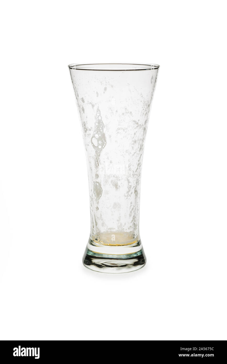 Empty pilsner glass isolated against white background. glass with foam on the inside. Stock Photo