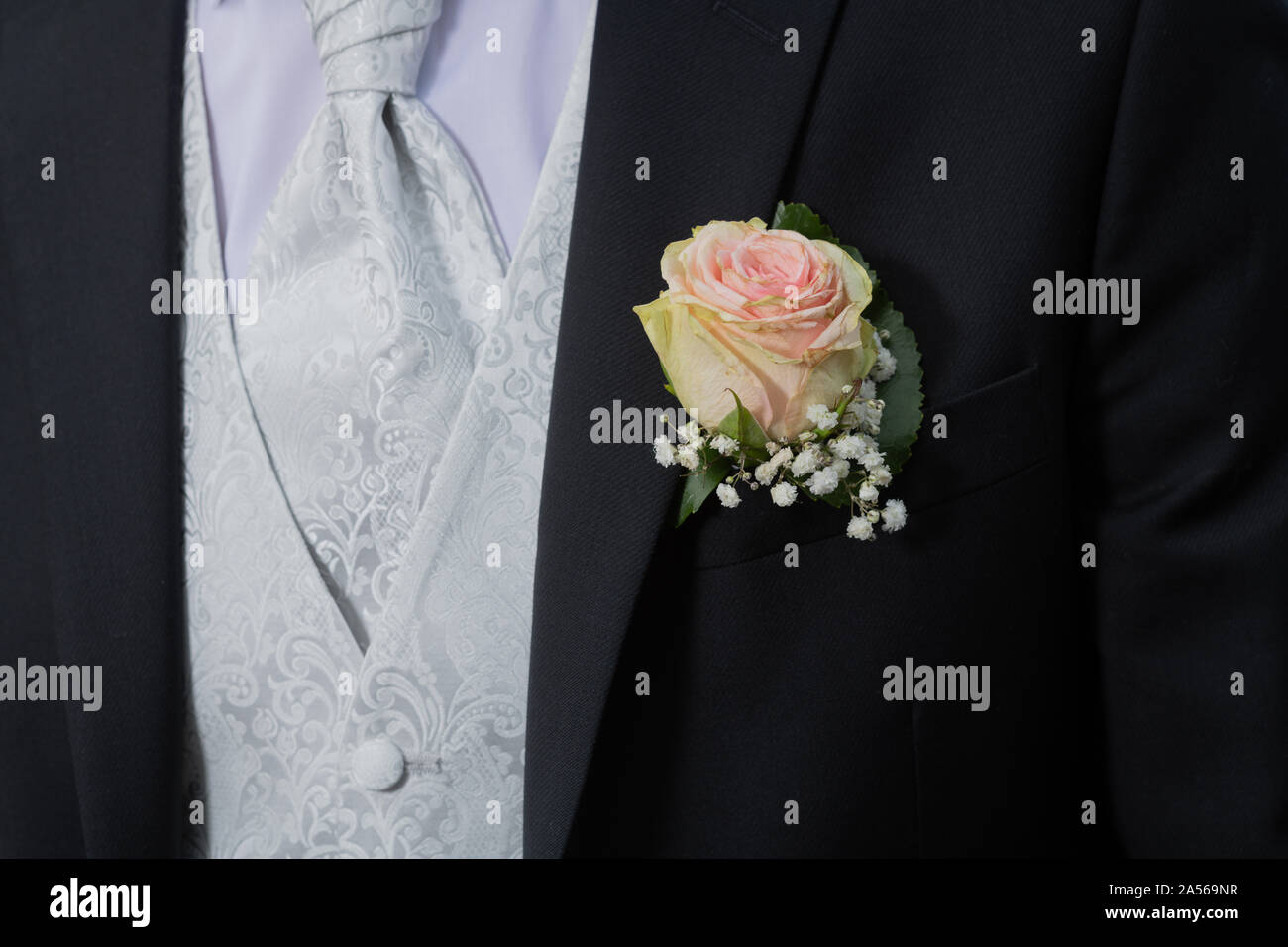 Symbole, Gesellschaft. Heiraten. Ein Hochzeitsanzug mit Weste und einer Rose am Revers . Stock Photo