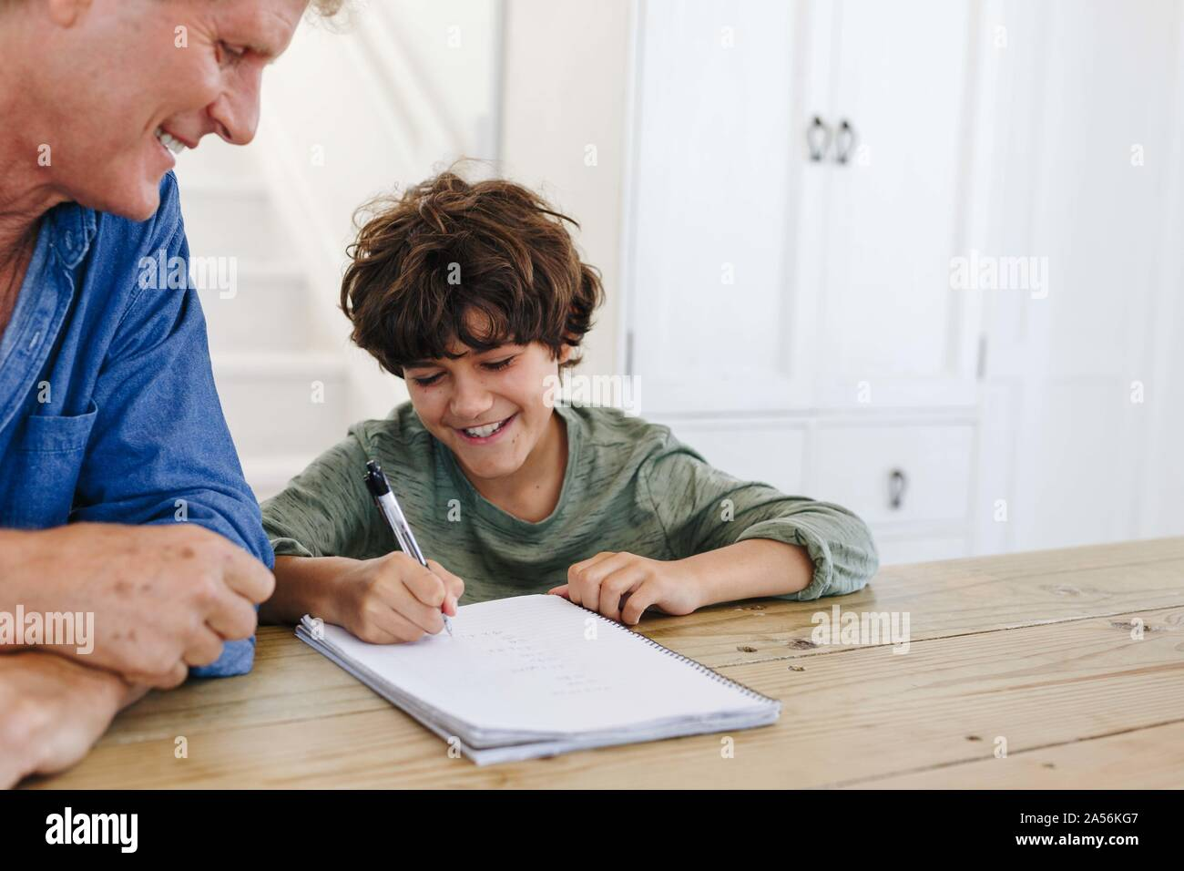 Father helping son with homework at home Stock Photo