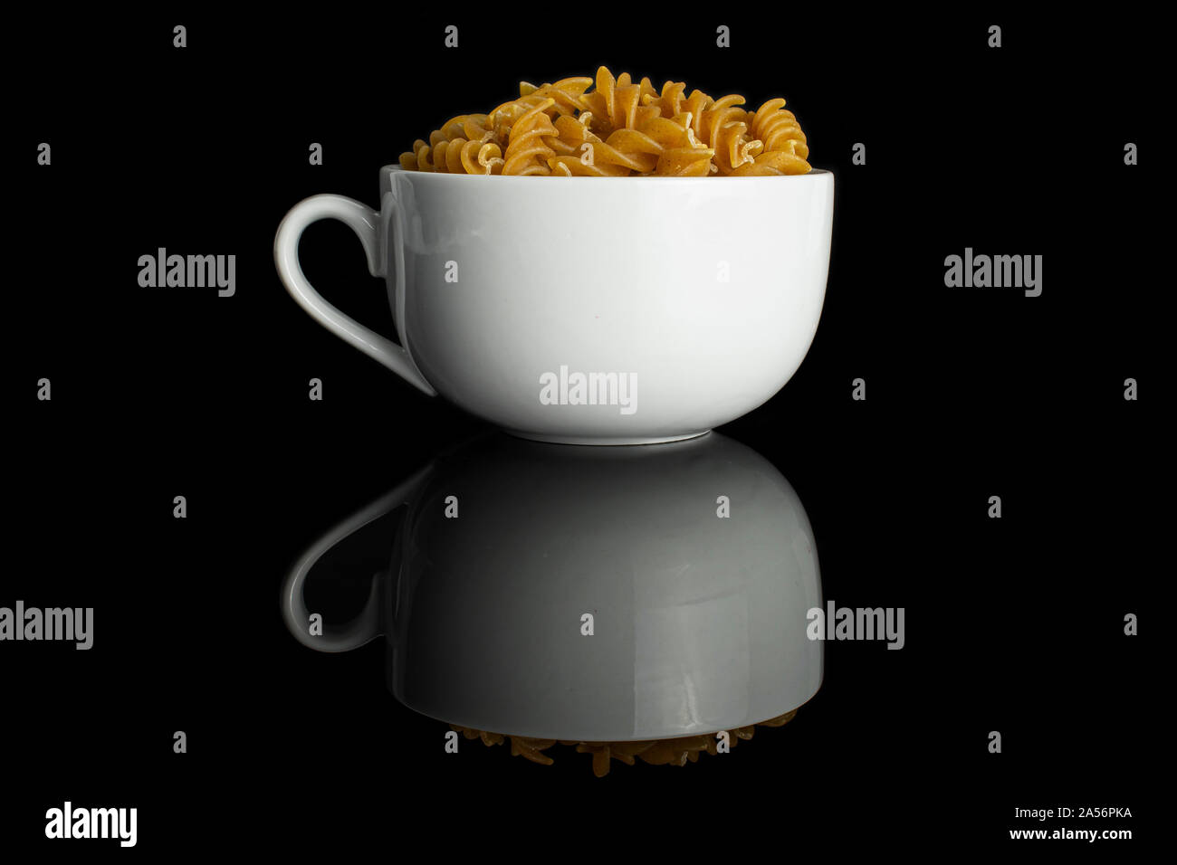 Lot of whole dry brown wholegrain fusilli in white ceramic cup isolated on black glass Stock Photo