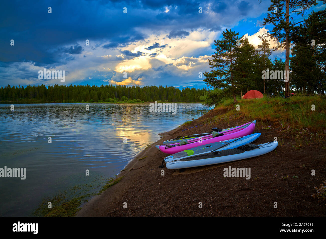 Storm clouds along Hebgen Lake with paddleboard and kayaks. Stock Photo