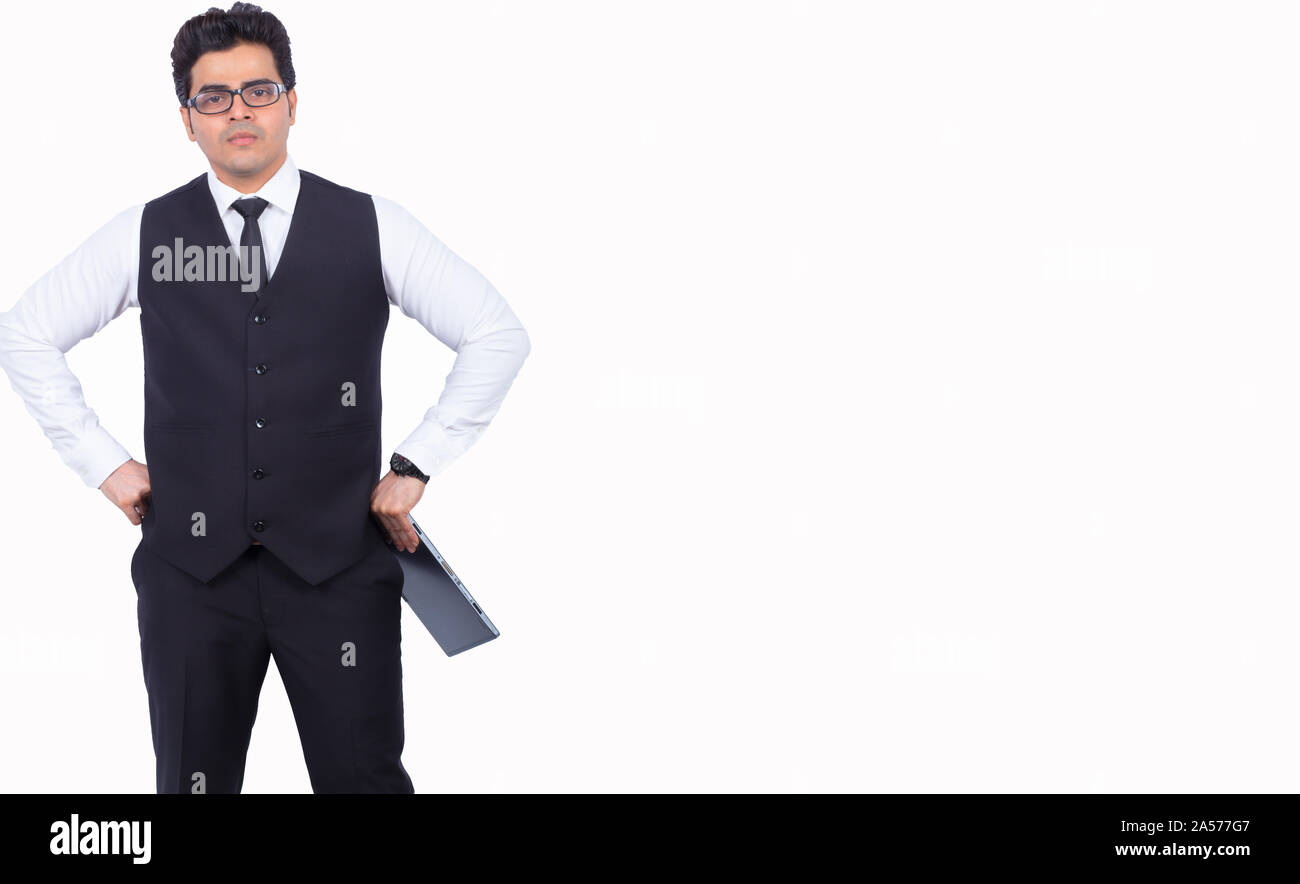 Handsome young businessman with digital tablet. Male professional is standing with hands on hips. He is wearing formals on white background. - Stock Photo