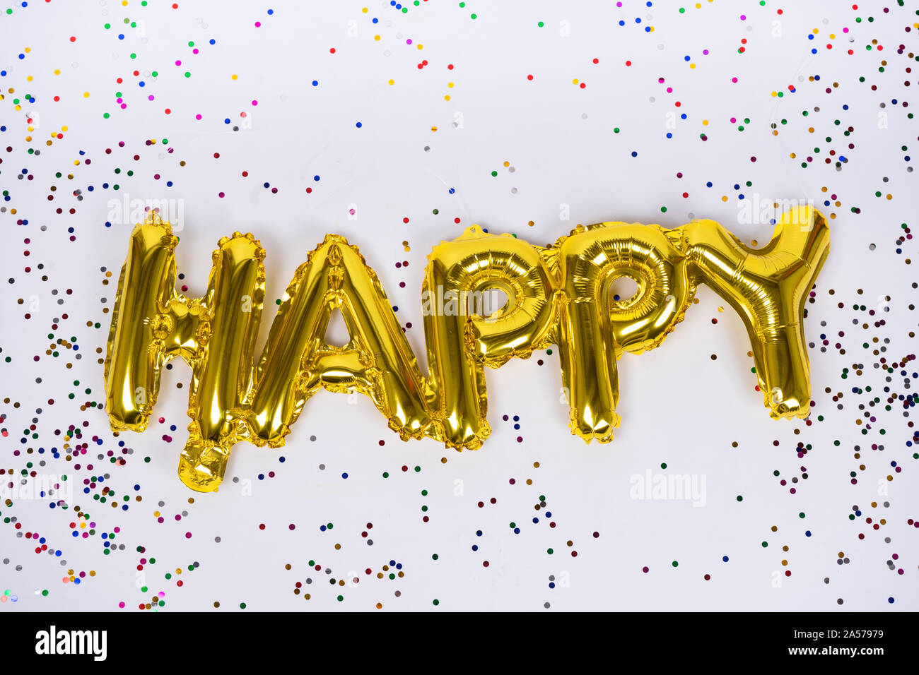 Happy letters of frustrated golden balloons isolated with colorful confetti on white background. Congratulations. Stock Photo