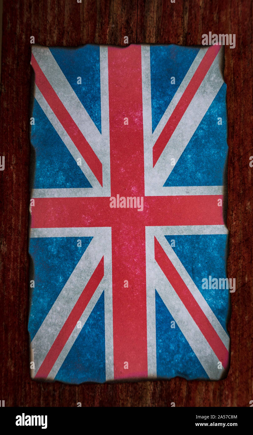 grungy burnt edges union jack flag on red wooden background Stock Photo