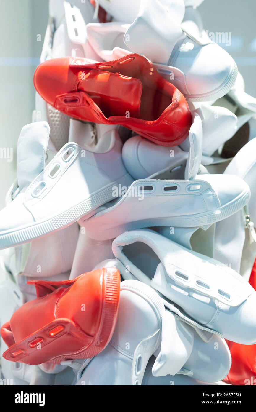 Glass basket with jogging shoes without shoe laces of white and red colors in shop Stock Photo