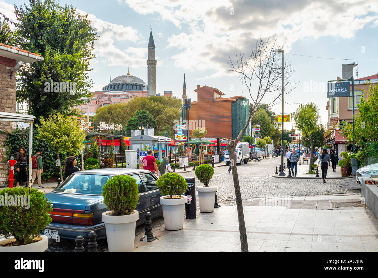 Hagia Sophia museum and mosque is visible in the distance near the Ottoman Life park on a street in the Sultanahmet district of Istanbul Turkey. Stock Photo