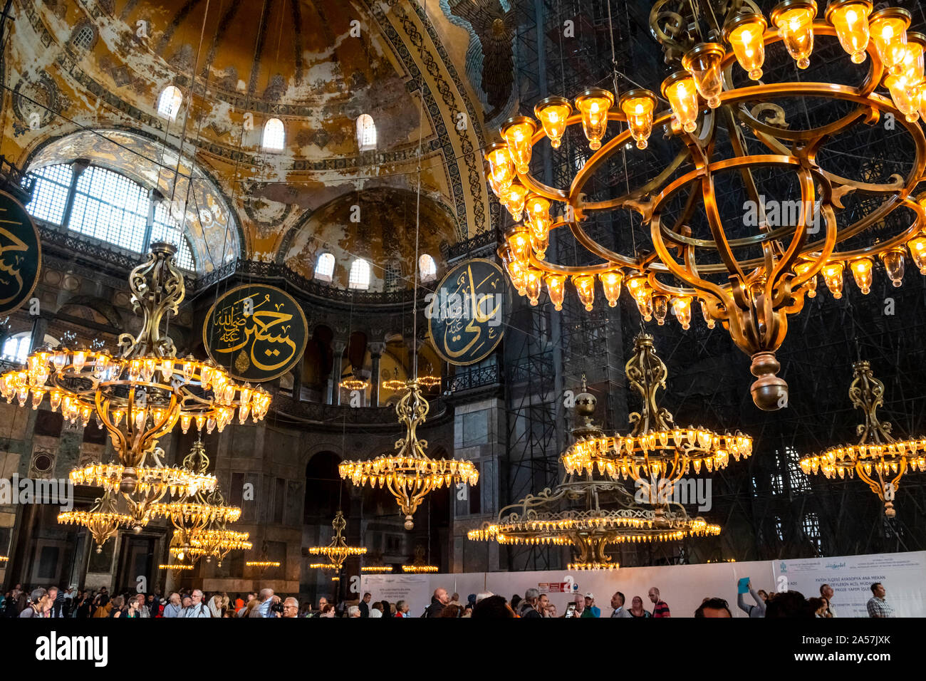 View of the ceiling and upper level as tourists gather under the chandeliers of the Hagia Sophia museum, a former Muslim Mosque, in Istanbul, Turkey. Stock Photo