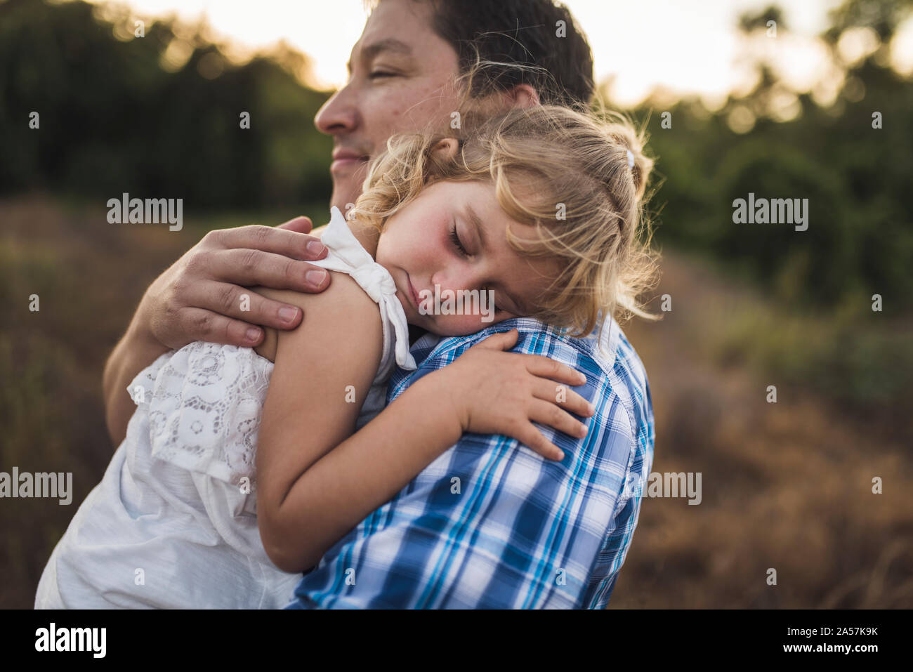 4 yr old girl asleep on her dad' shoulder - B/W photo Stock Photo