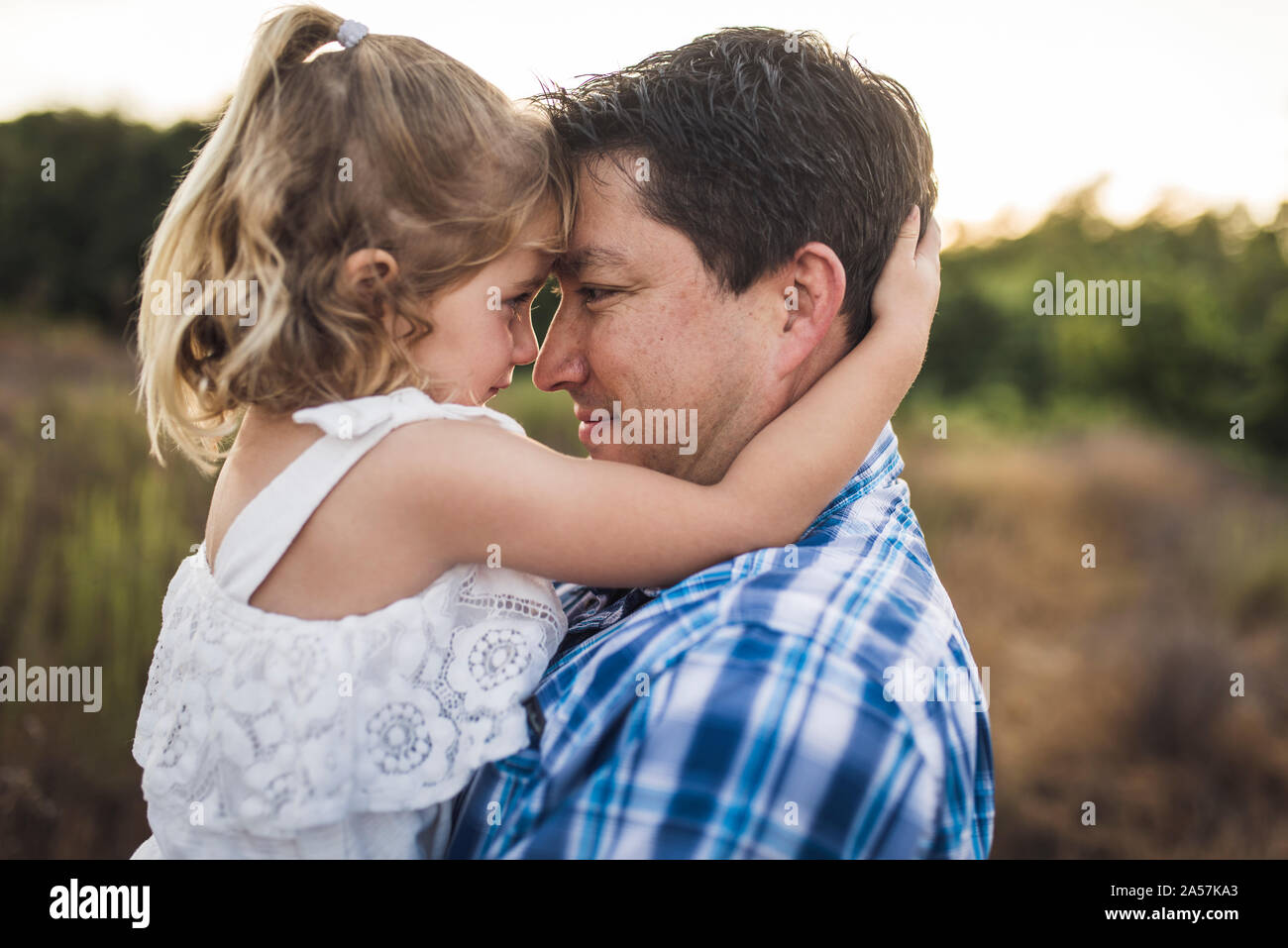 Young girl looking into dad's eyes while touching foreheads Stock Photo