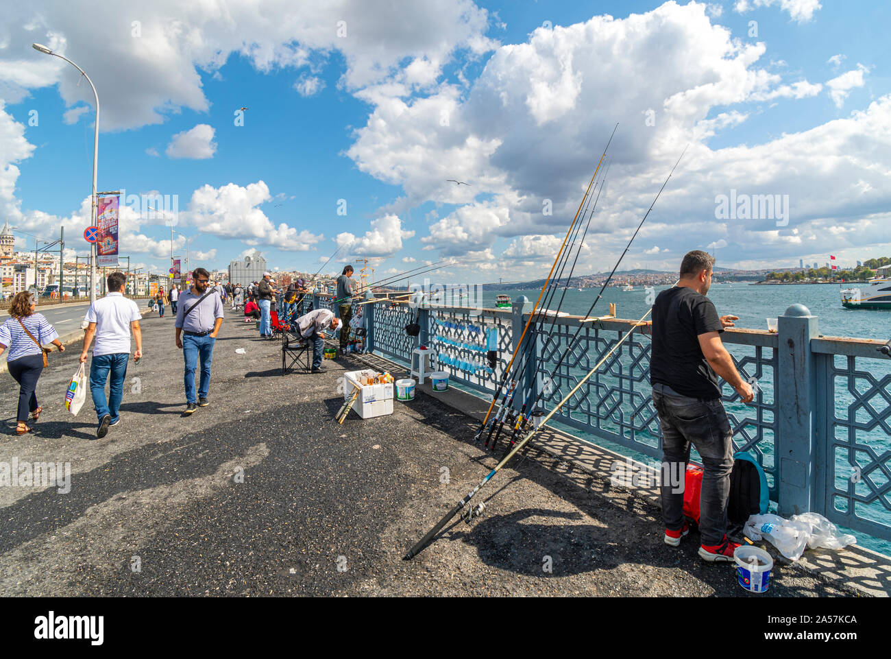 Local Turkish fishermen hang their fishing poles off the Galata Bridge over the Bosphorus at the Golden Horn. Stock Photo