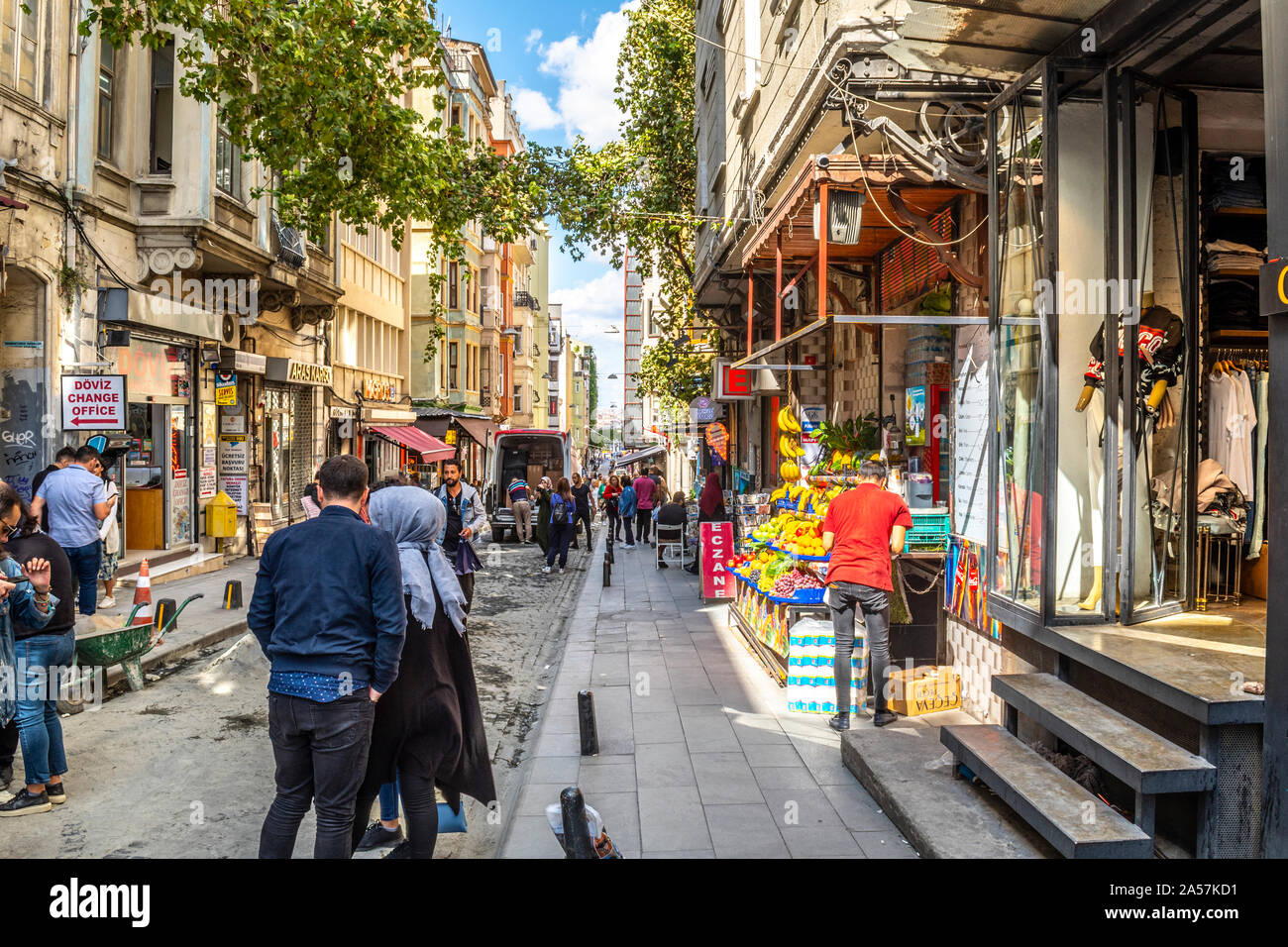A busy street in the Galata Karakoy district of Istanbul Turkey with fruit stand, shops, tourists, Turks and street construction, in Istanbul Turkey. Stock Photo