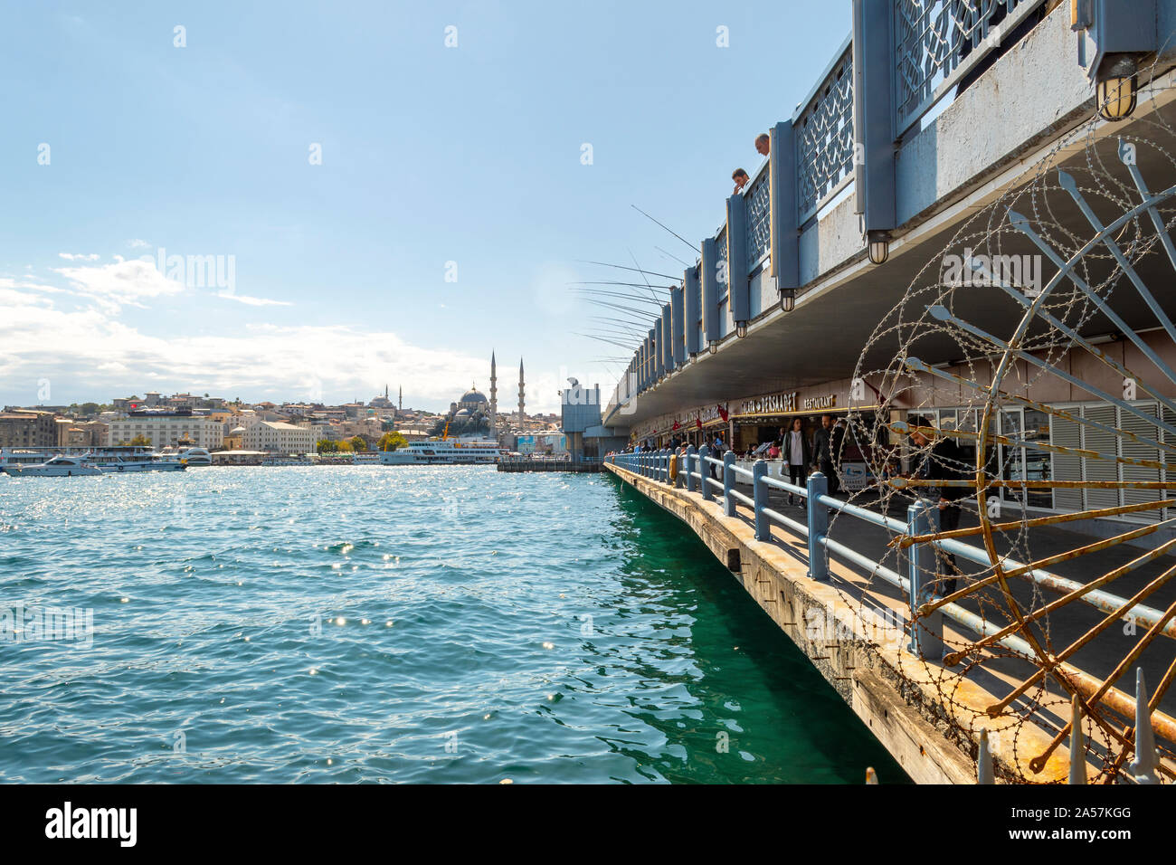 Two levels of the Galata Bridge over the Bosphorus River in Istanbul Turkey, with cafes, tourists, fisherman with poles and the city in view. Stock Photo