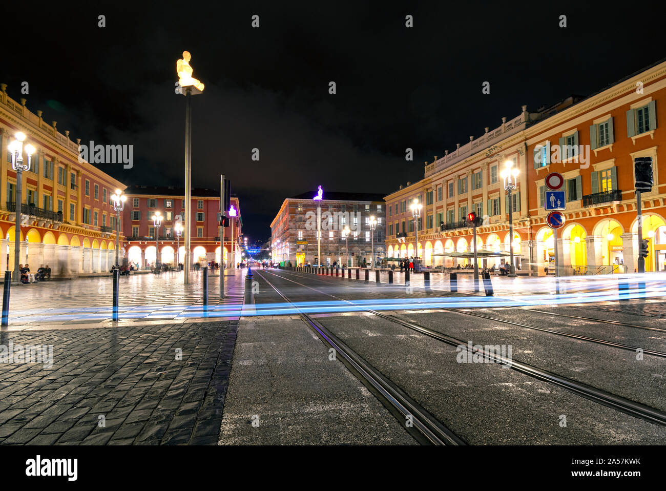 Car headlights make light trail from long exposure as the cross tram tracks late at night in Place Massena in the historic city of Nice, France. Stock Photo