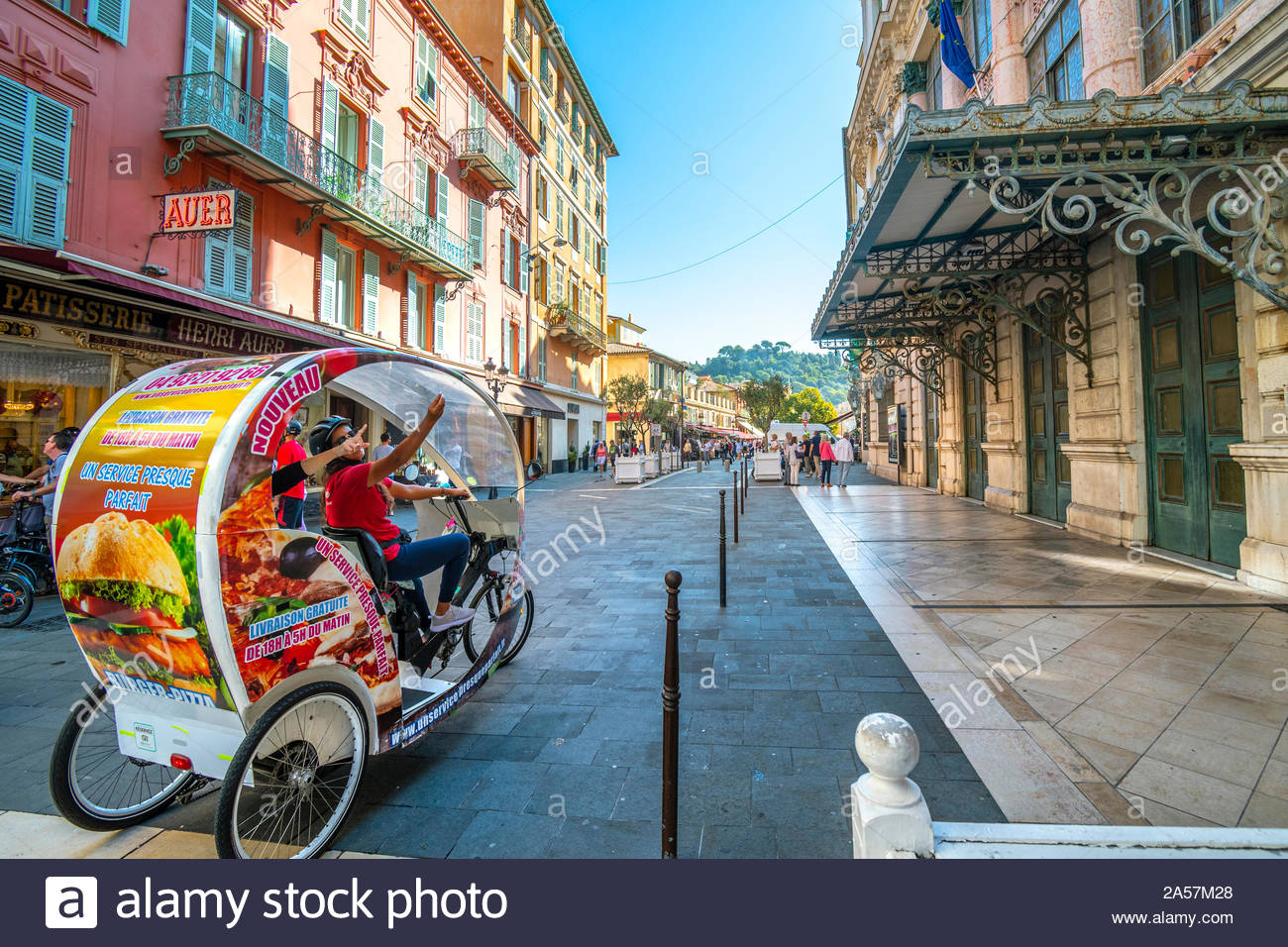 A female cyclist taxi driver guides tourists on a 3 wheel rickshaw bicycle through the Old City of Nice, France on the French Riviera. Stock Photo
