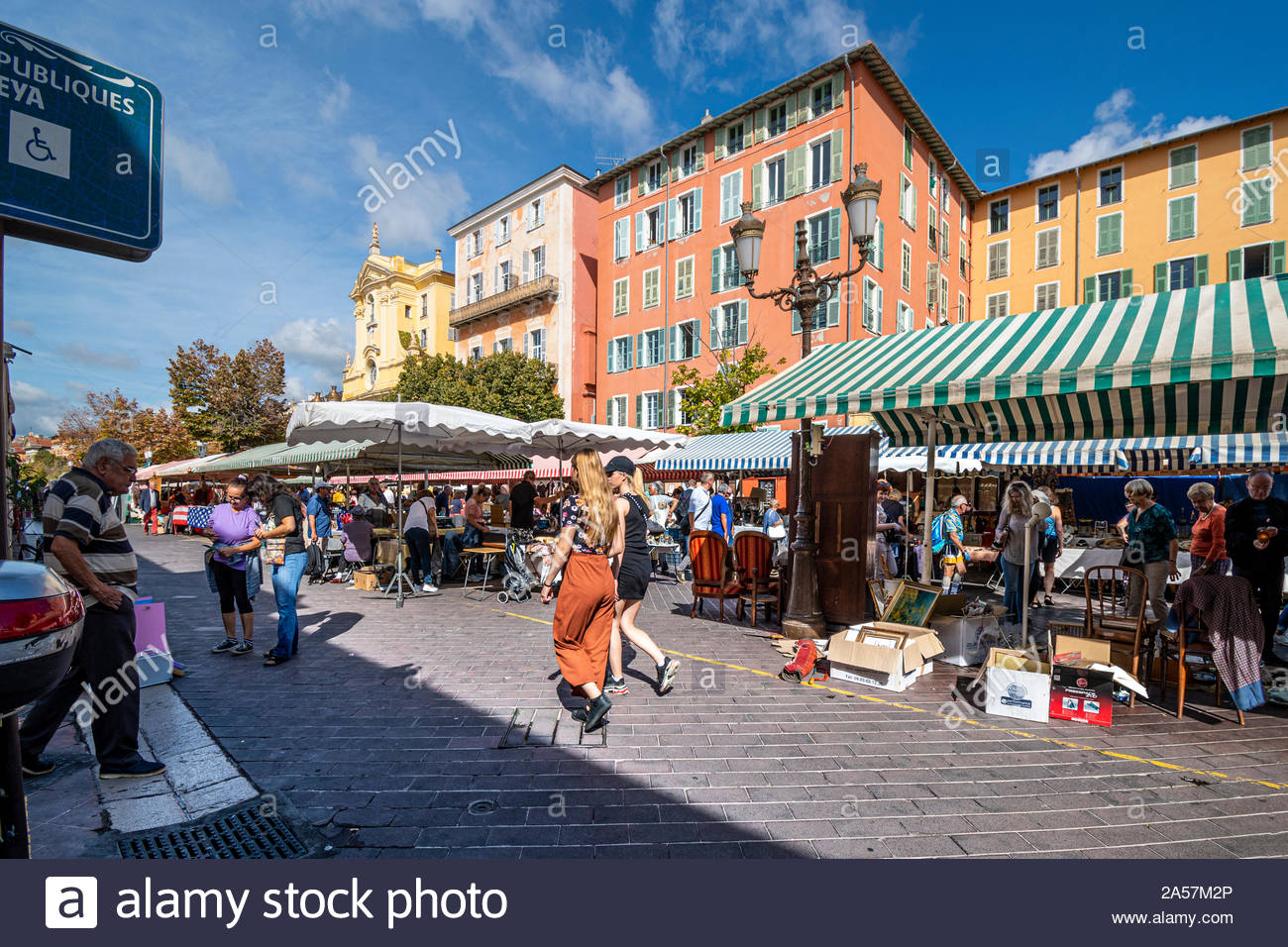 Tourists and local French enjoy a summer day in the outdoor Cours Saleya flea market marketplace in Old Town Nice France on the Riviera Stock Photo
