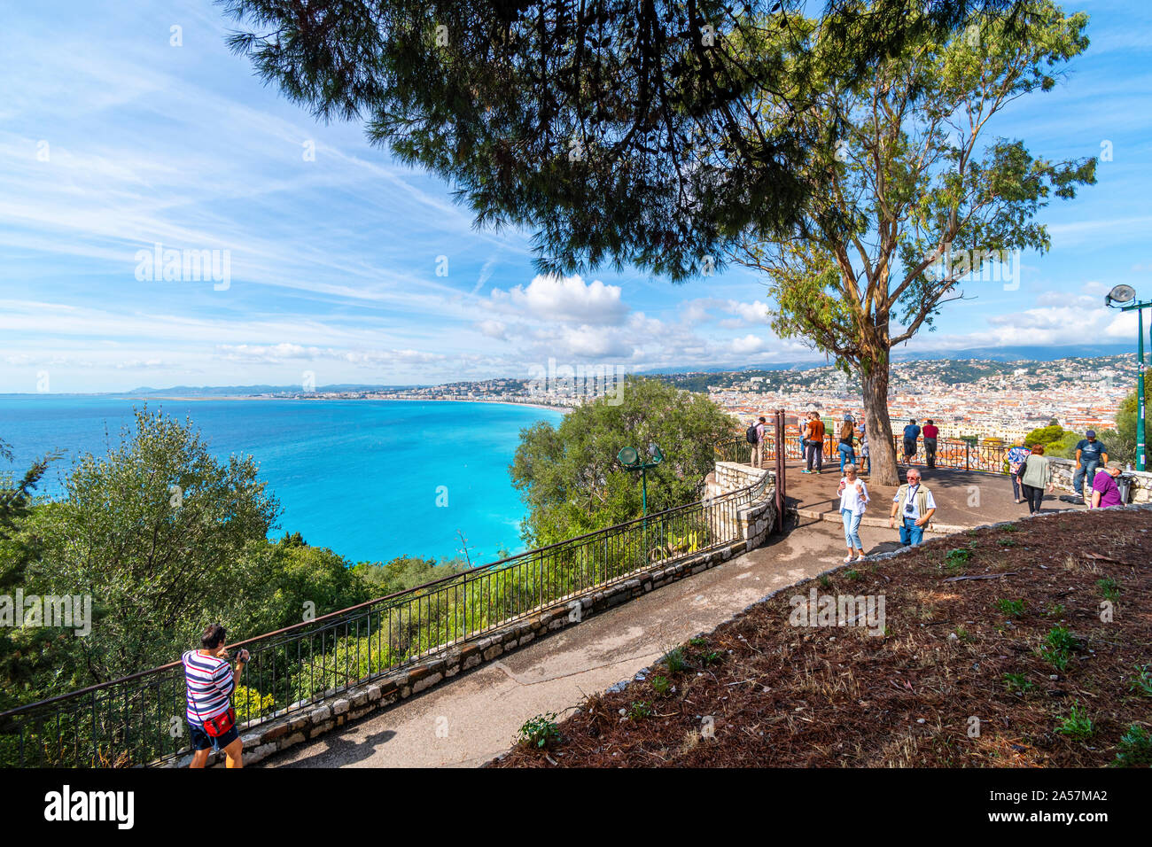 Tourists enjoy a summer day on Castle Hill overlooking the turquoise Mediterranean Sea and the city of Nice France, on the Riviera Stock Photo