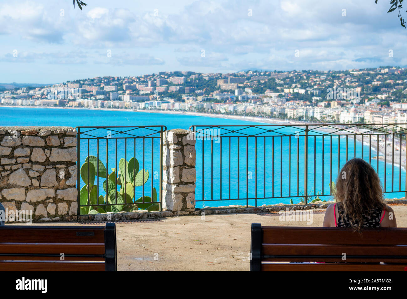 A woman sits on a bench from a lookout at Castle Hill overlooking the Mediterranean Sea, Bay of Angels, beach and city of Nice, France. Stock Photo
