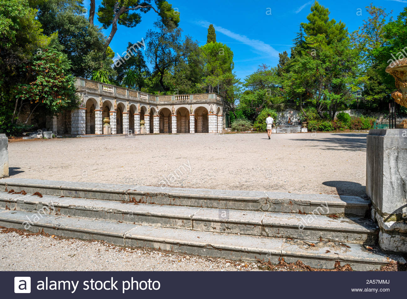 A solo female traveler walks through a gravel courtyard near an arched Roman building on Castle Hill in Nice, France. Stock Photo