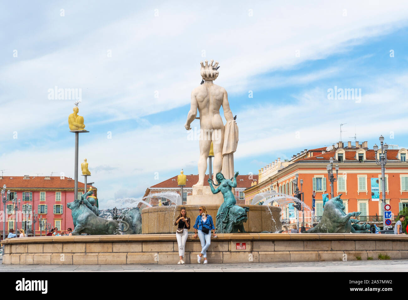 Two women relax in front of the Apollo Statue at the Fountain of the Sun in Place Massena, in the city of Nice France, on the French Riviera. Stock Photo