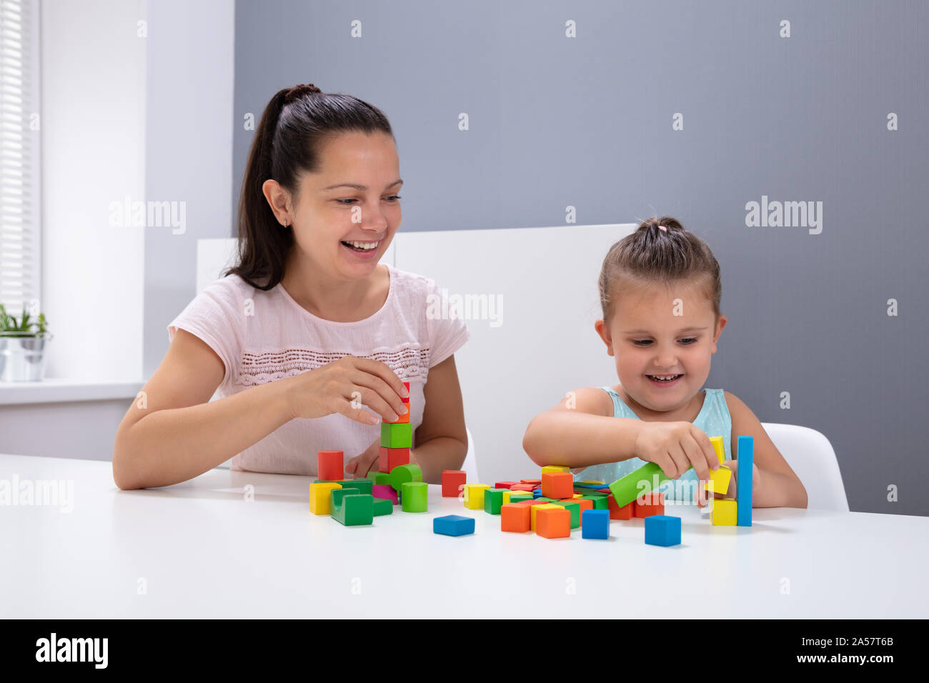 Smiling Daycare Worker Playing With Child Stacking Building Blocks On White Desk Stock Photo