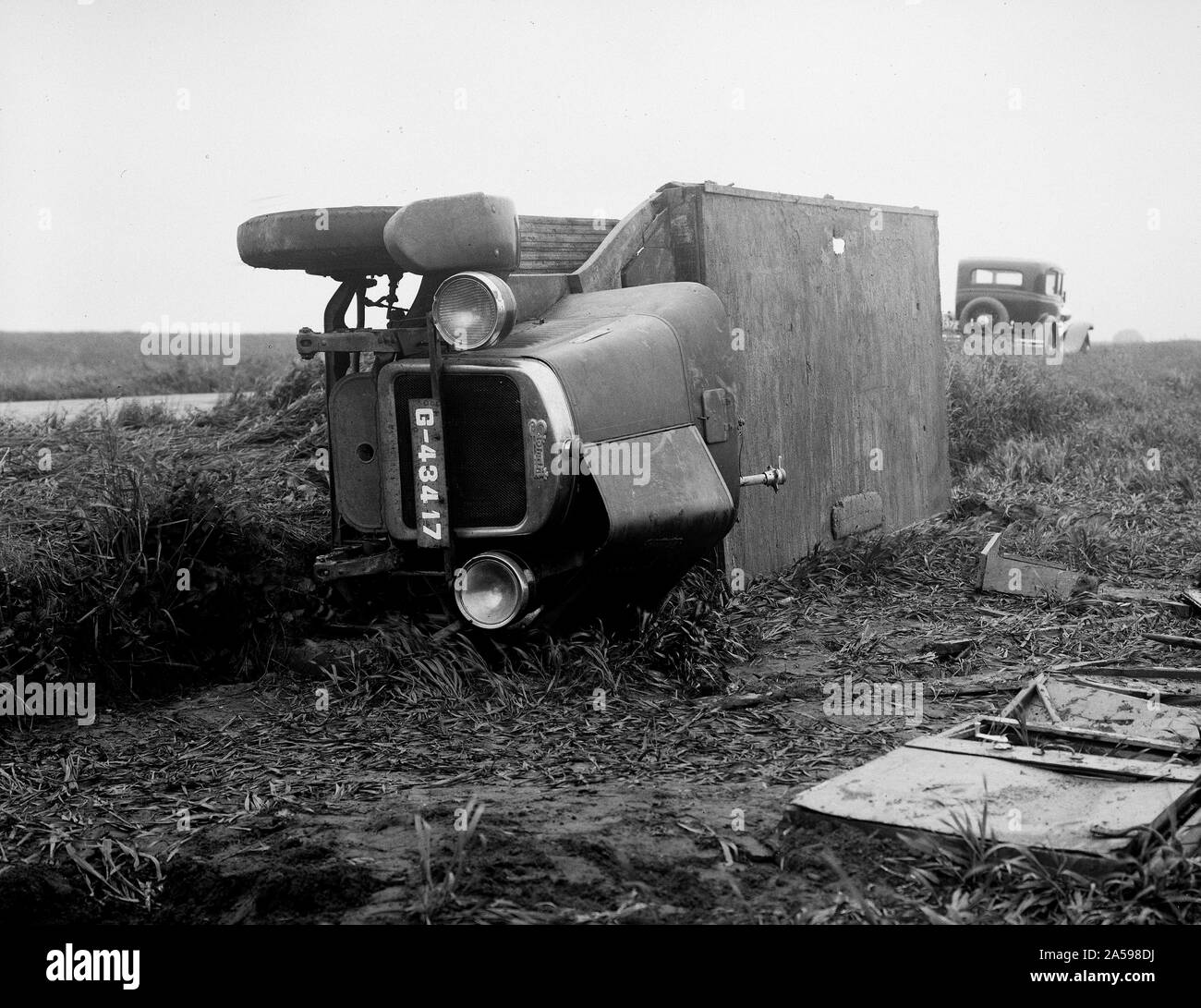 Traffic accident with tilted passenger car on the roadside ca. 1930 Stock Photo