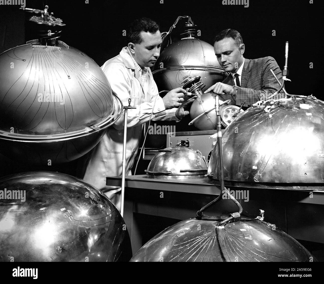 An engineer and technician at the National Aeronautics and Space  Administration (NASA) Lewis Research Center install the instrumentation on  spherical fuel tanks for an investigation of the behavior of liquids in  microgravity