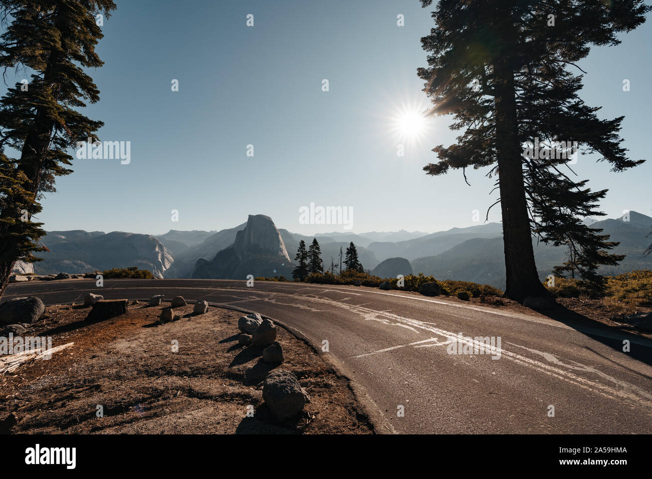 Beautiful curvy road down to Yosemite Valley with view to Half Dome Mountain Stock Photo