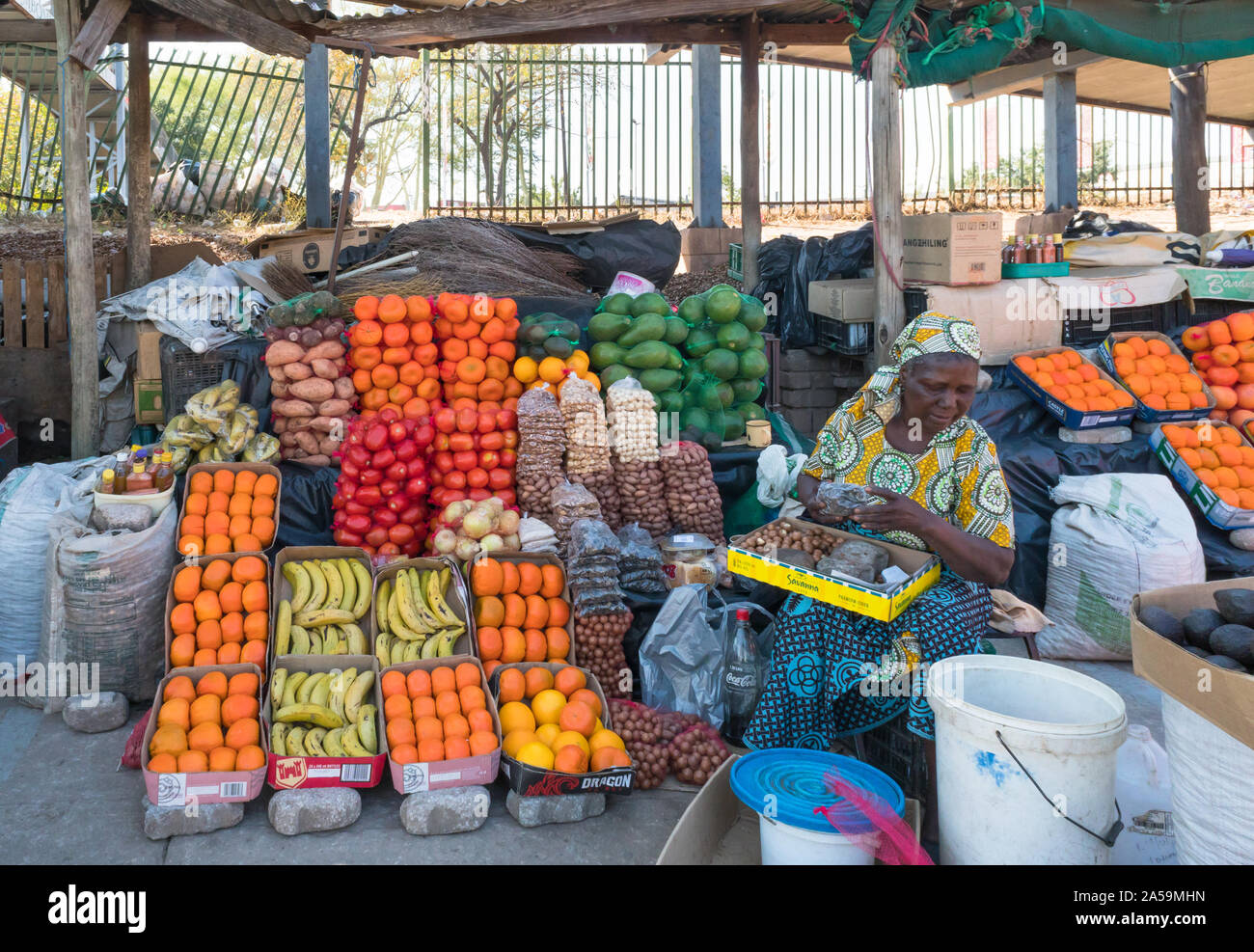 woman selling fruits, trader, vendor at a street market stall in Hazyview, Mpumalanga, South Africa Stock Photo