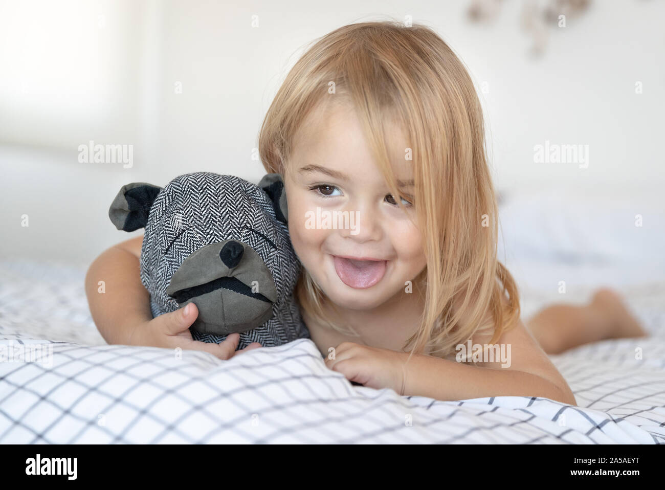 Portrait of a happy little baby boy having fun at home, lying down on the bed with favourite soft toy and making faces, enjoying childhood Stock Photo