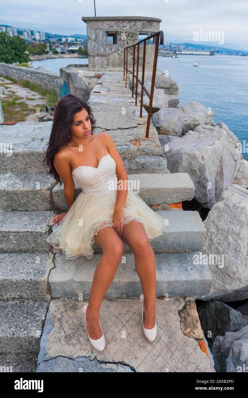 Teenager girl in prom dress outdoors looking away single sitting seated on steps staircase whole body stiletto legs leg beauty Stock Photo
