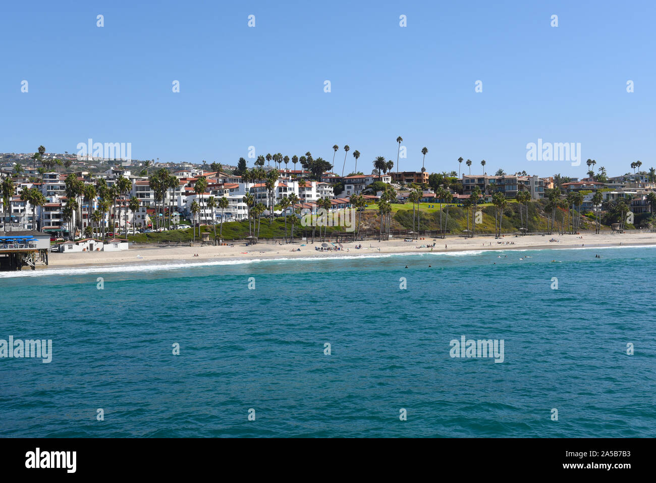 SAN CLEMENTE, CALIFORNIA - 18 OCT 2019: The beach and coastline with surfers and sunbathers seen from the pier in the South Orange County beach town. Stock Photo