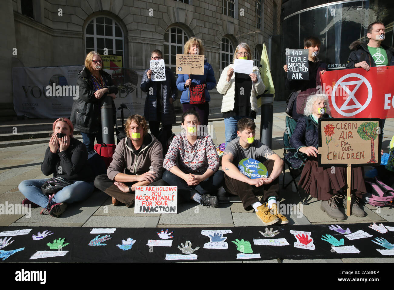 Manchester, UK.19th October, 2019.  A small group of climate protesters are holding a one hour silent protest to raise awareness of what they say is a lack of action taken by Manchester City Council despite declaring a climate emergency earlier in the year. St Peters Square, Manchester, Lancashire, UK. Credit: Barbara Cook/Alamy Live News Stock Photo