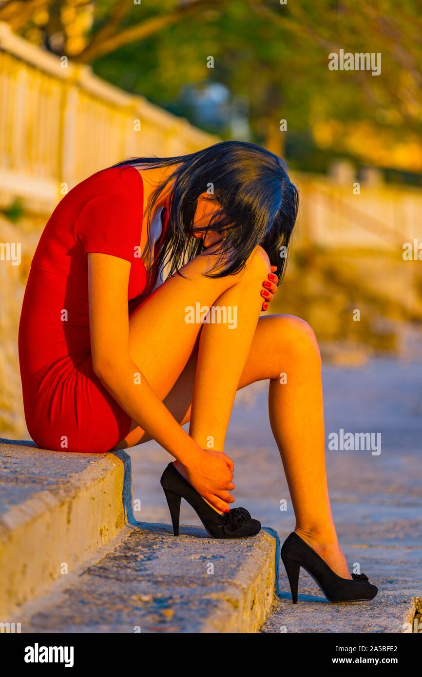 Deeply-upset teenager girl sitting on waterfront lit by intensive hot warm sunset light outdoors sideview side-view leggy legs leg Stock Photo