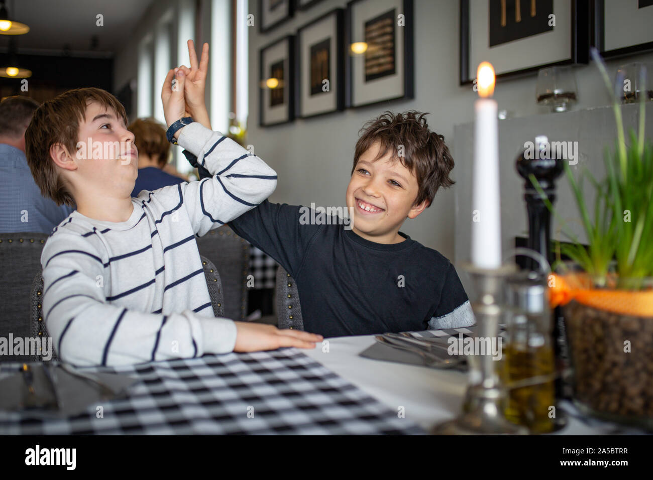 Two boys waiting for pizza in a restaurant.  - brothers having fun. Stock Photo