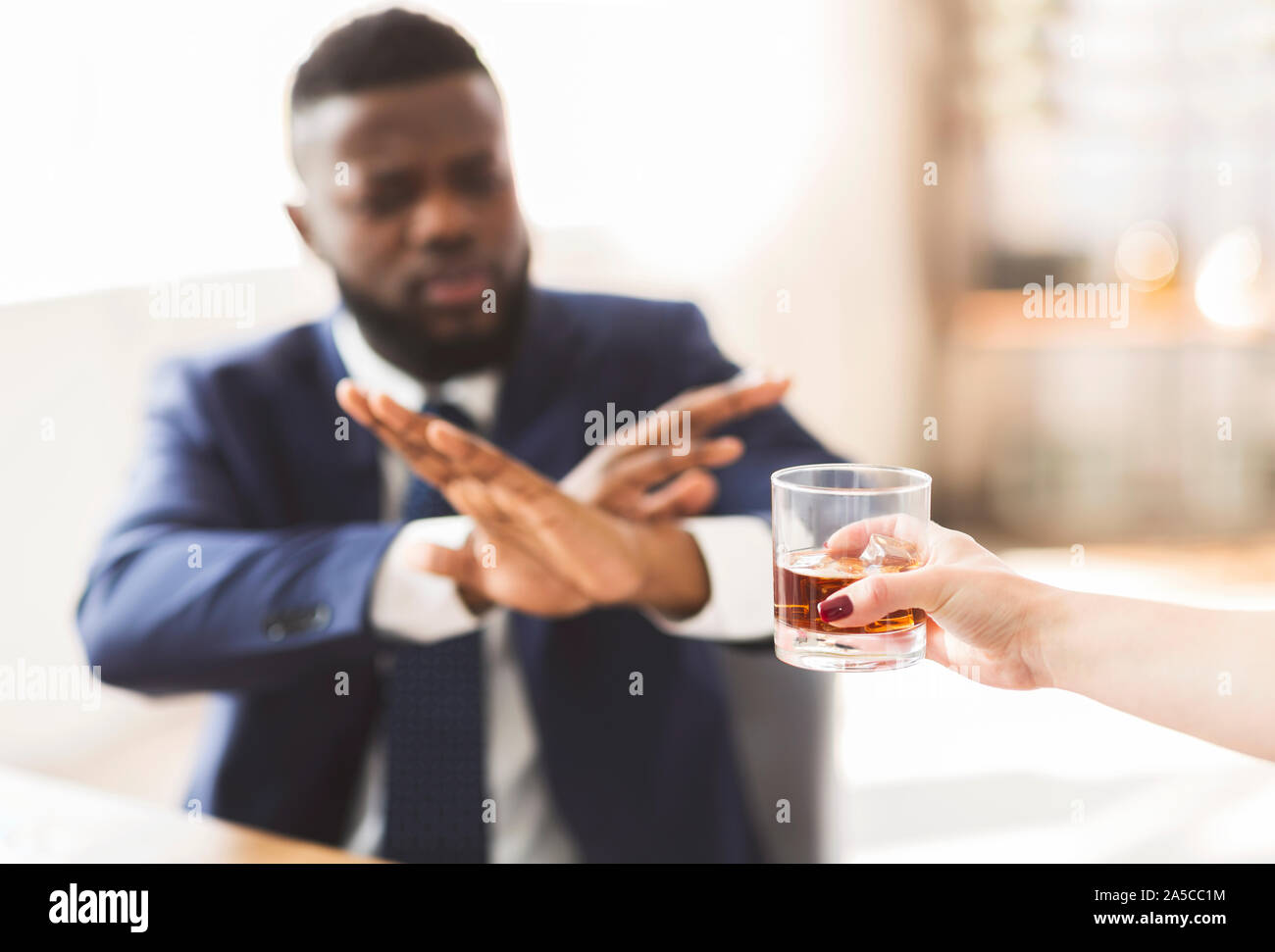 Businessman showing no sign to glass of whiskey Stock Photo