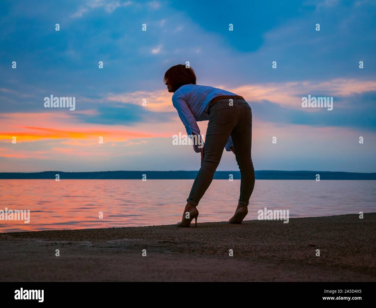 Post sunset waterfront attractive woman standing bending-over looking away spread legs wearing denim pants high-heels inviting sexual allurement Stock Photo