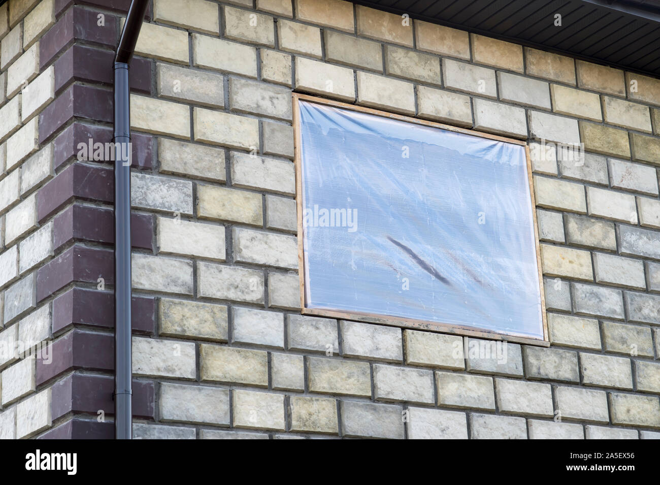 The wall of a new brick house with a window opening covered with film. The concept of completion, lack of money, inflation. Stock Photo