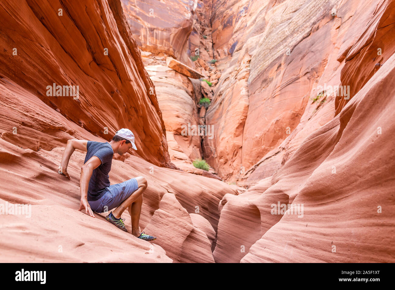 Orange red wave sandstone abstract formations and man climbing rocks at narrow Antelope slot canyon in Arizona on trail from Lake Powell Stock Photo