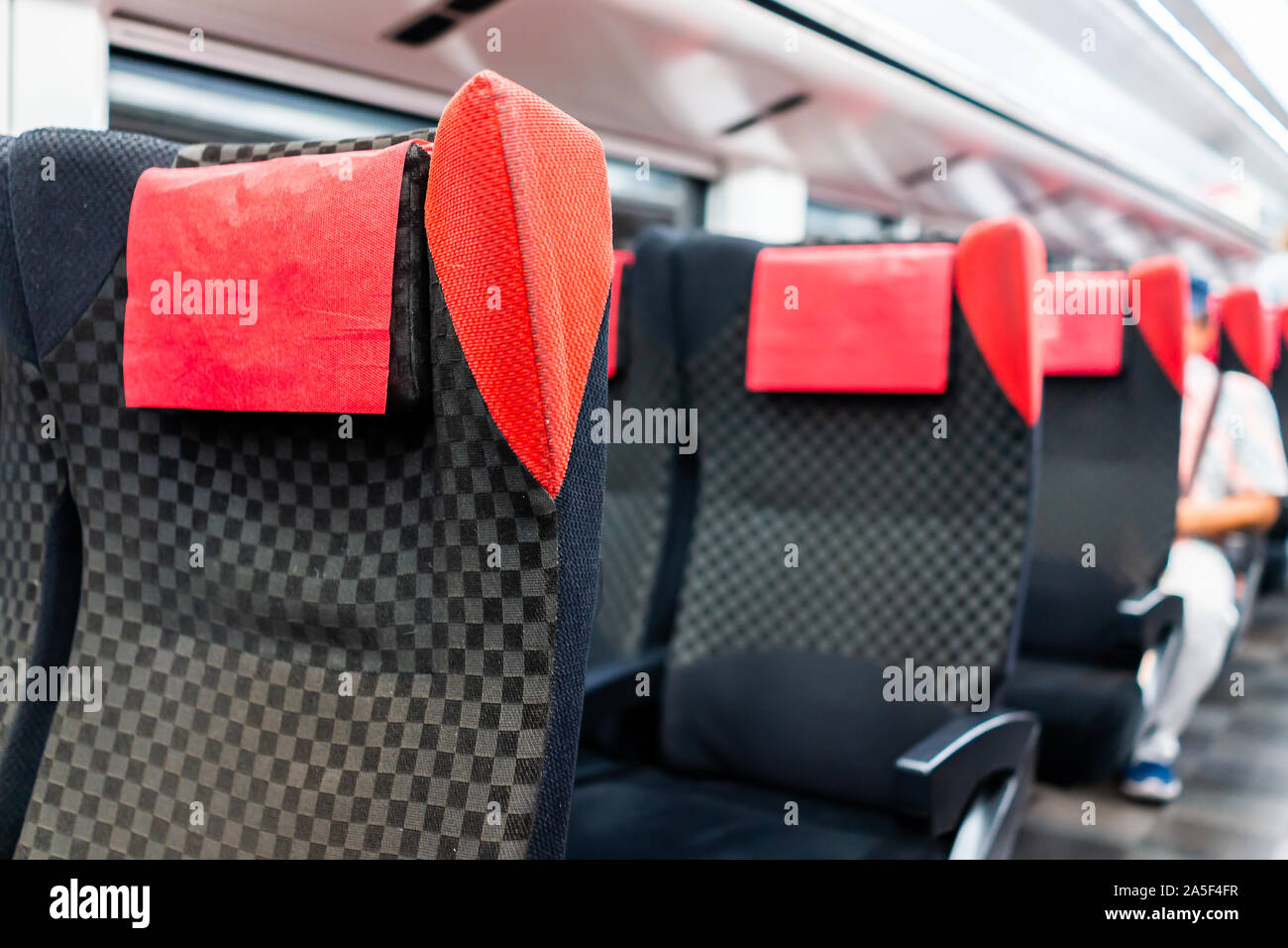 Empty red comfortable chairs seats row closeup in aisle in subway train interior inside with person sitting in background and modern comfy seating Stock Photo