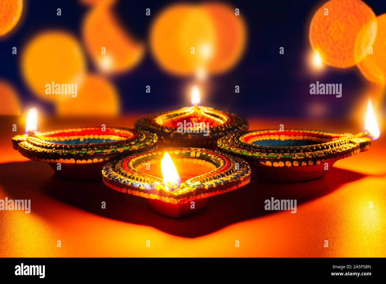 Indian festival Diwali, Diya oil lamps lit on colorful rangoli. Hindu traditional. Happy Deepavali. Copy space for text. Stock Photo
