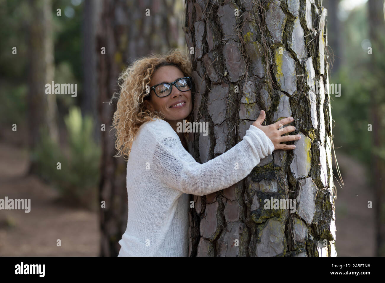 one woman hugging with close eyes a old tree on the forest - love and affection at the wood - save the forest and climate change concept - respect nat Stock Photo