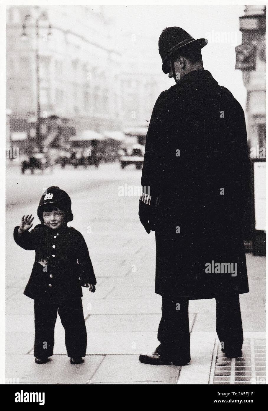 Vintage black and white postcard showing 1937 Bobbys (Policemen) with young boy dressed in uniform, view of 1930s London in background. Stock Photo