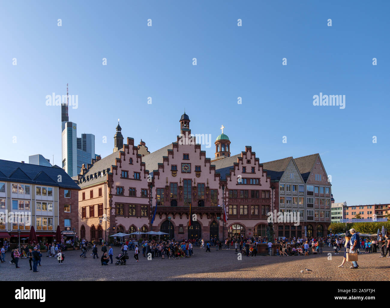 Outdoor sunny view of old town at Römerplatz, historical market square, surrounded with Römerberg, timber medieval German house, and city hall. Stock Photo