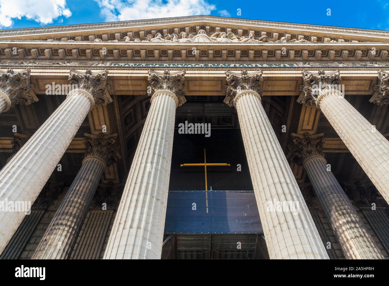 Low-angel shot of the Roman Catholic church La Madeleine in Paris. The impressive columns are holding the sculptural pediment showing the Last... Stock Photo