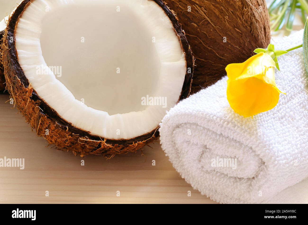 Coconut,  white towel and tropical flower on wooden background. Wellness or spa relax concept. Stock Photo